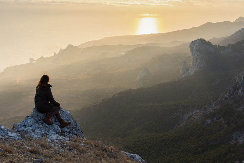A girl stands on a mountain and looks at the sunset. atmospheric evening view of the mountains