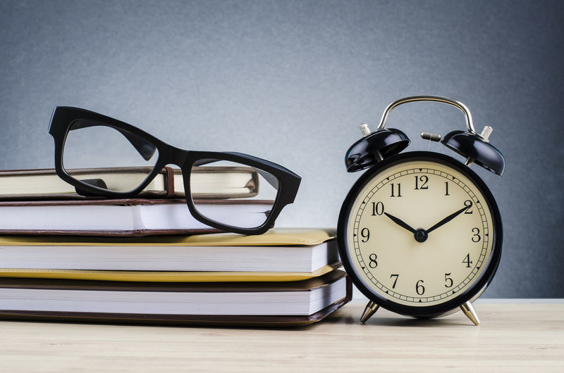 alarm clock, and spectacles on stacking book over dark background, Glasses Alarm Clock Clock Eyeglasses  Indoors  Table Time Close-up Still Life No People Number Studio Shot Single Object Wood - Material Fashion Publication Accuracy Education Group Of Objects Personal Accessory Eyewear Clock Face