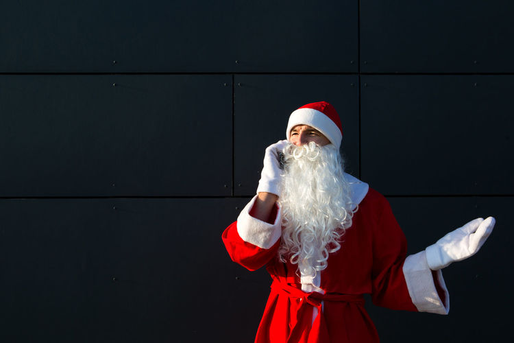 Man wearing santa clause costume talking on phone while standing against wall outdoors