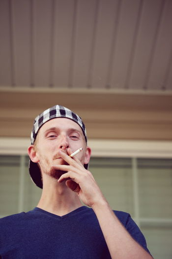 Low Angle View Of Man Smoking Against Building