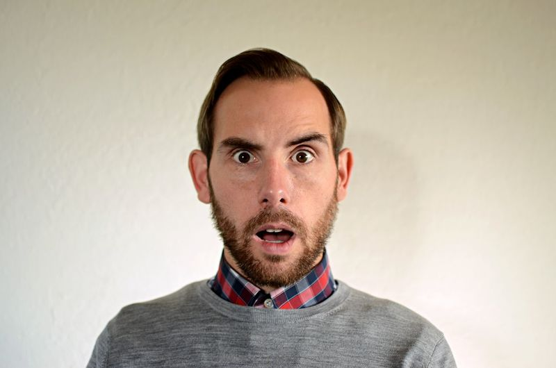 Man With Surprised Look Raised Eyebrow Beard Close-up Headshot Looking At Camera Mouth Open Portrait Receding Hairline Studio Shot Young Adult
