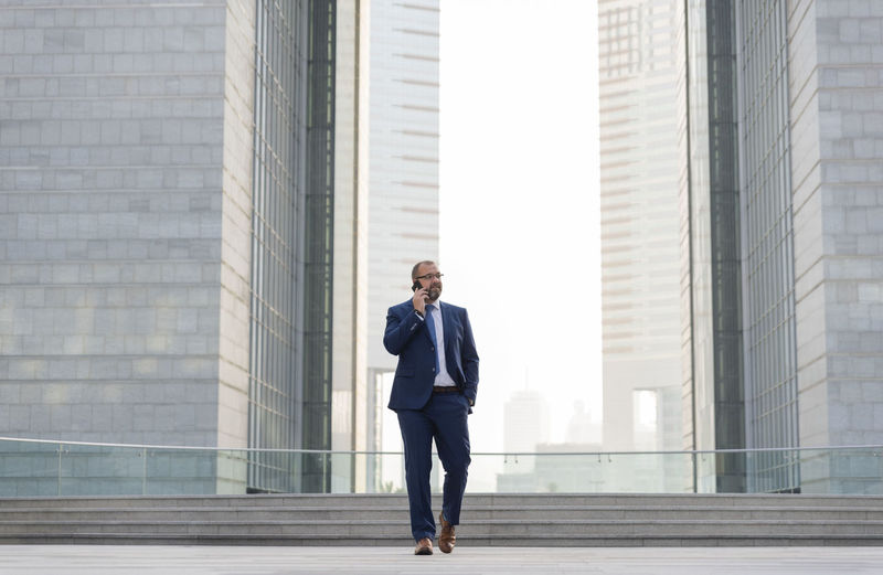 Full length of businessman talking on mobile phone while walking against office buildings