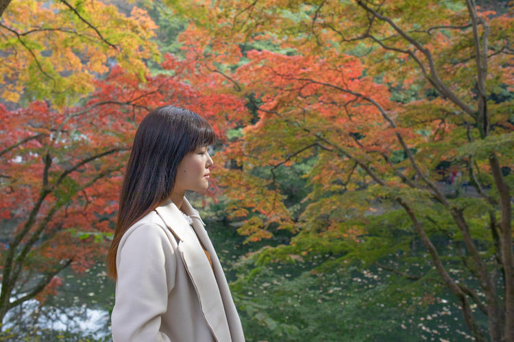 Side view of young woman standing against trees during autumn
