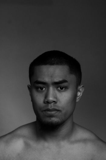 Portrait of young man against gray background