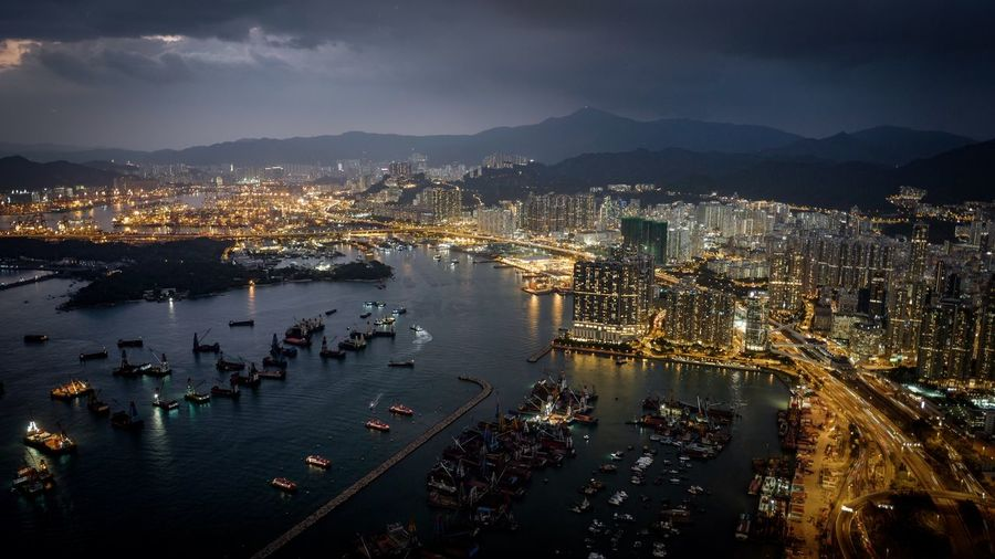 High Angle View Of Victoria Harbour By Illuminated Cityscape At Night