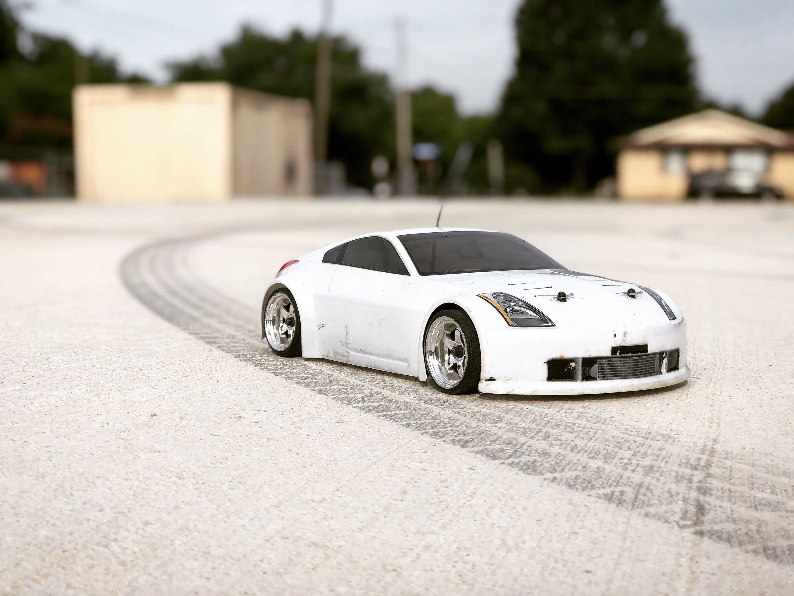 transportation, car, mode of transportation, motor vehicle, land vehicle, architecture, building exterior, built structure, day, road, no people, selective focus, focus on foreground, city, street, retro styled, toy, wealth, outdoors, luxury, wheel