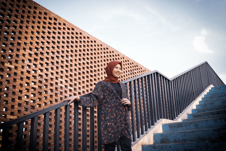 Low angle view of woman wearing hijab standing on staircase against sky