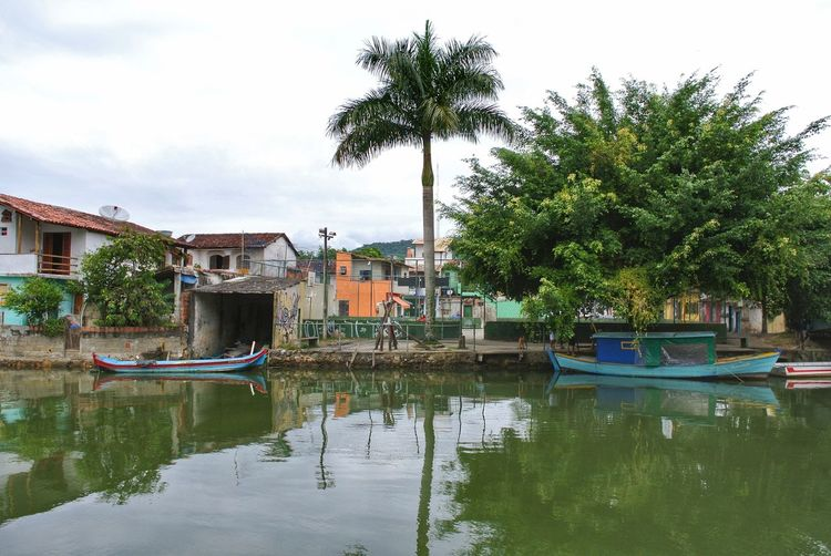View of swimming pool by canal against sky
