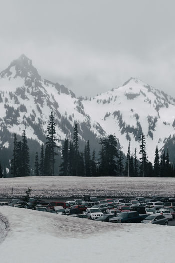 Cars Parked At Parking Lot Against Snowcapped Mountains