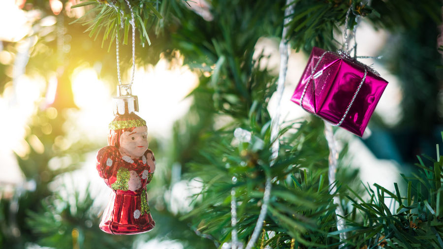 Close-up of gift box and figurine hanging on christmas tree
