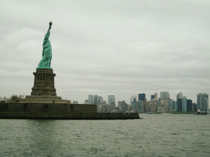 Statue Of Liberty By Hudson River Against Cloudy Sky
