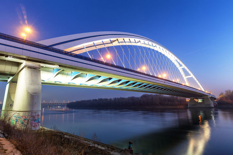 Illuminated bridge over river against sky at dusk