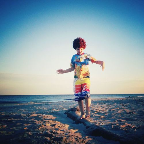 Boy walking at beach against sky during sunset