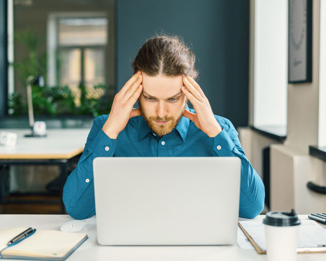 Focused male company employee trying to concentrate