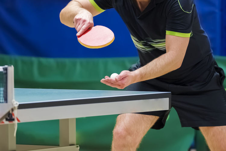 Table Tennis player serving Sport Competition One Person Real People Lifestyles Sports Clothing Playing Exercising Athlete Racket Men Racket Sport Leisure Activity Competitive Sport Midsection Determination Healthy Lifestyle Strength Tennis Skill  Tennis Racket Effort Table Tennis Serving Ping Pong