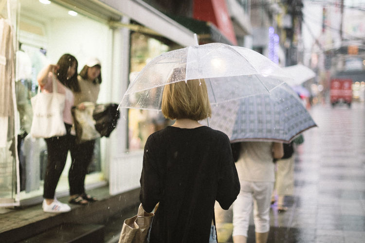 Rear View Of Woman Holding Umbrella While Walking On Street During Rainy Season