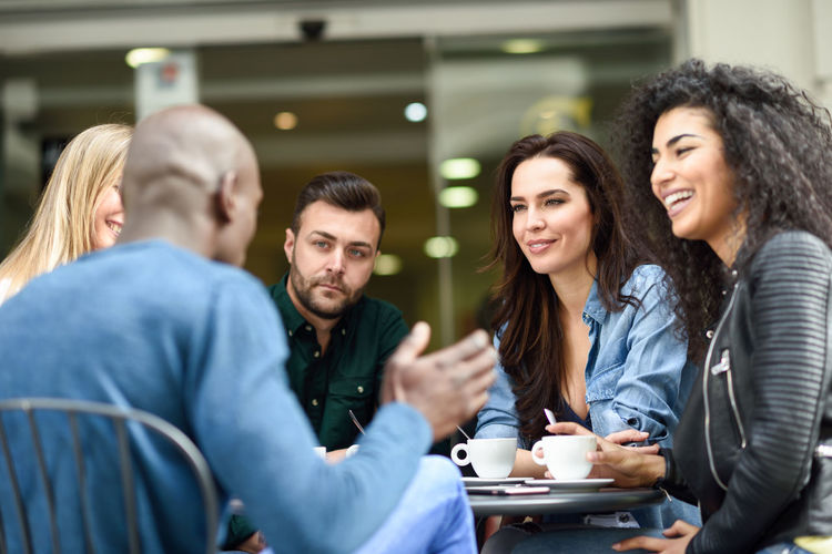 Multiracial group of five friends having a coffee together. Three women and two men at cafe, talking, laughing and enjoying their time. Lifestyle and friendship concepts with real people models Group Of People Young Adult Smiling Adult Women Young Women Togetherness Happiness Friendship Sitting Drink Food And Drink Emotion Waist Up Coffee - Drink Young Men Casual Clothing People Coffee Coworker