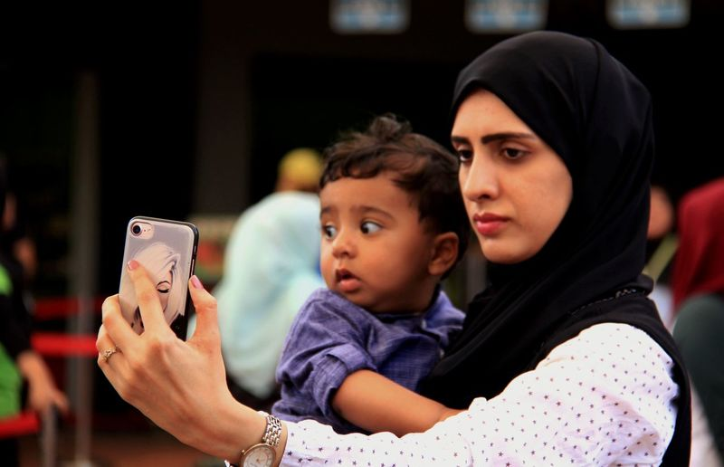 Close-up of mother taking selfie with toddler son in city