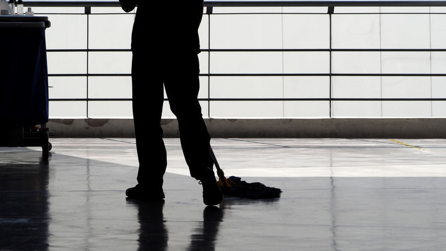 Low section of silhouette man cleaning floor