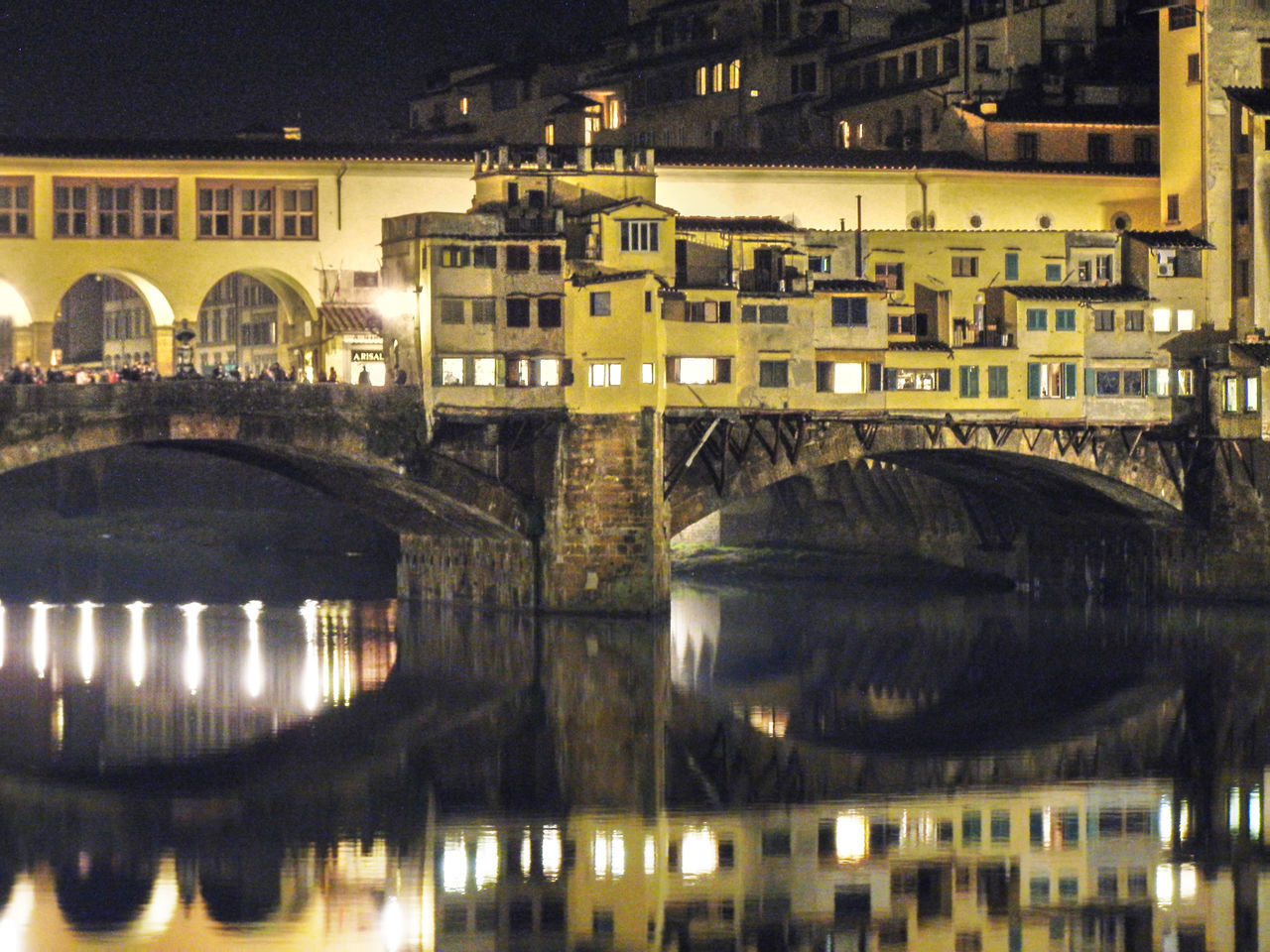 ARCH BRIDGE OVER RIVER IN CITY AT NIGHT