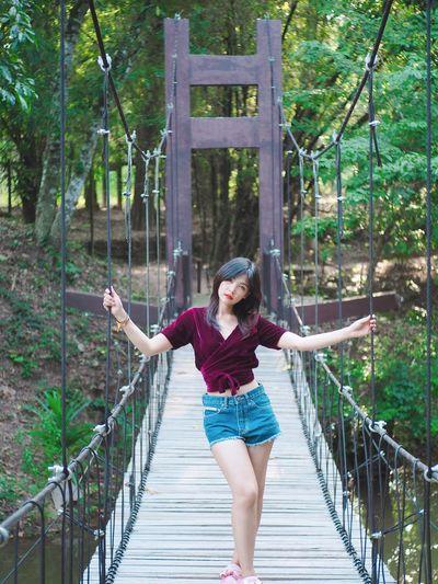 Portrait of woman standing on footbridge in forest