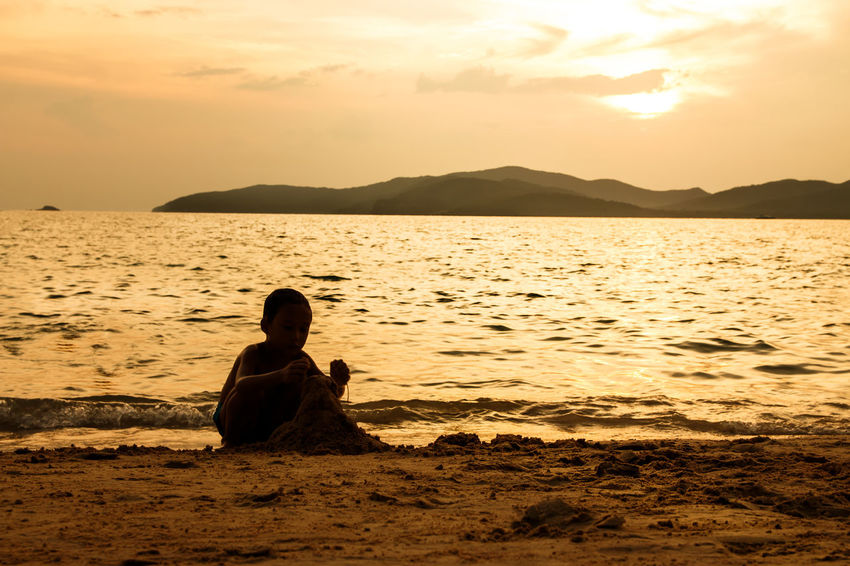 silhouette of people at the beach,The beauty of natural light at sunset. Sky Sunset Real People Beauty In Nature Water Sitting Lifestyles Scenics - Nature Leisure Activity One Person Sea Beach Mountain Tranquil Scene Tranquility Nature Land Idyllic Cloud - Sky Outdoors Silhouette Happiness Happy People Holiday Relaxing Children Women Man Romantic Orange Clouds And Sky Love Family Summer Sunrise Boy Freshair Freedom Fun