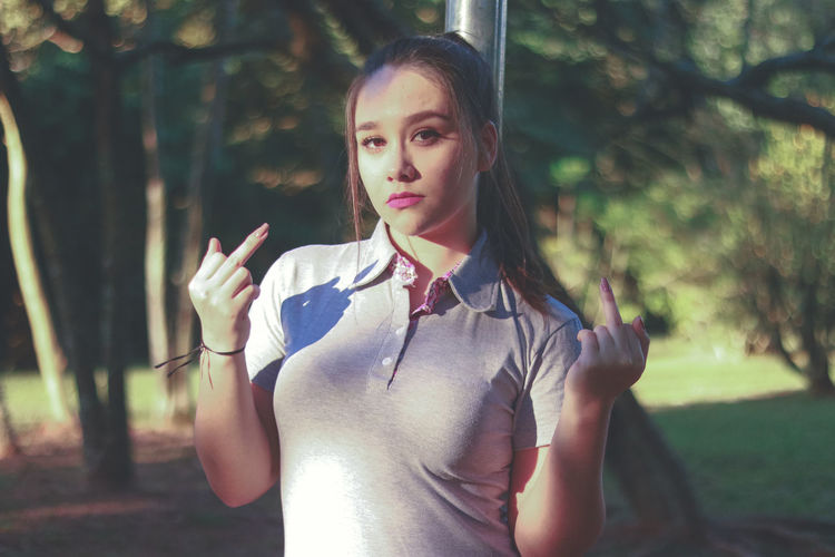 Portrait of beautiful woman showing middle fingers while standing at park