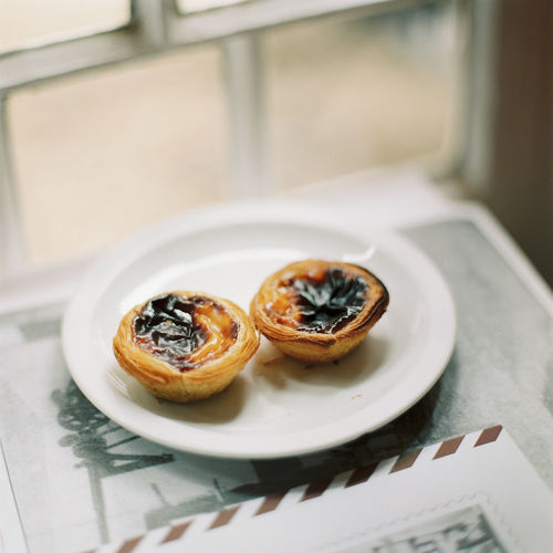 Close-Up Of Portuguese Custard Tarts On Plate On Table