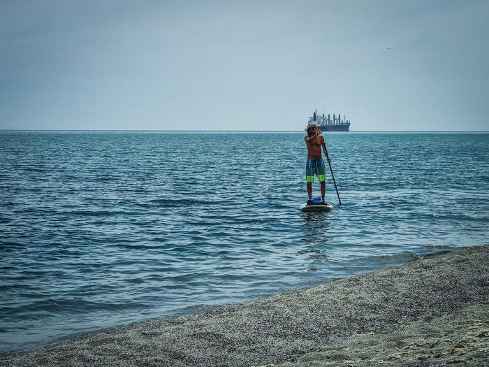 Rear view of man on sea against sky