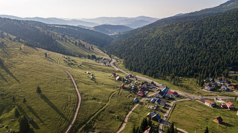 Aerial view of village by mountains