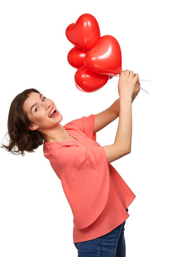 Young woman with red balloons against white background