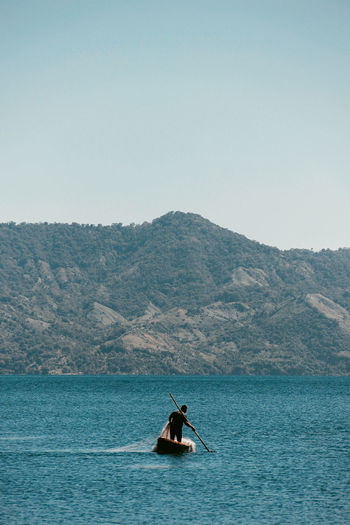 Man Rowing Boat In Sea Against Mountains