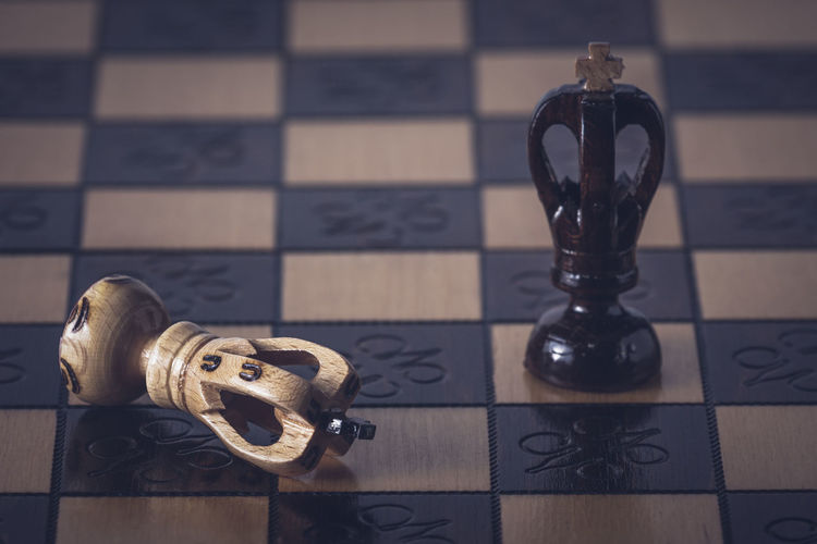 Close-up of chess pieces on tiled floor