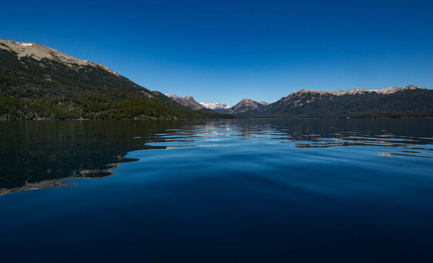 Scenic view of nahuel huapi lake by mountains against clear blue sky - villa la angostura