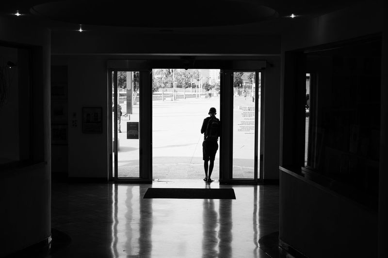 Rear view of silhouette man standing at doorway
