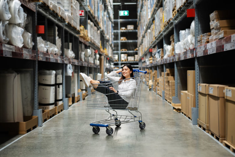 Full length of young woman sitting on shopping cart in warehouse