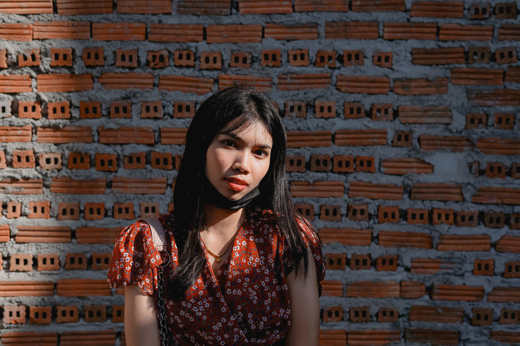 Portrait of woman against brick wall