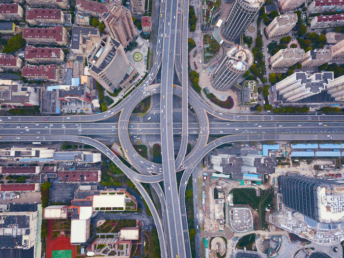 Aerial view of highway junctions with roundabout. Bridge roads shape circle in structure of architecture and transportation concept. Top view. Urban city, Shanghai, China. Shanghai China City Cityscape Buildings Architecture Downtown District Financial Road Street Building Exterior Aerial View Built Structure Residential District Building Connection Office Building Exterior High Angle View City Life No People Modern Transportation Skyscraper Highway Outdoors Overpass Multiple Lane Highway