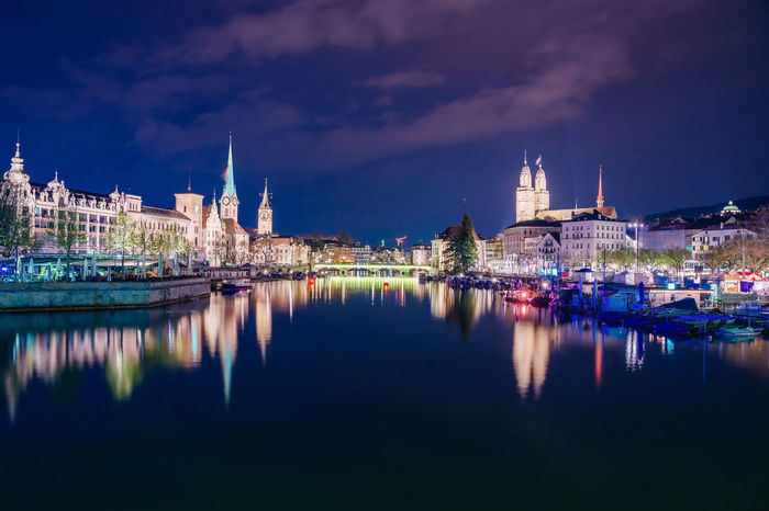 Panoramic view of historic Zurich city center with famous Fraumunster, Grossmunster and St. Peter and river Limmat at Lake Zurich on twilight blue sky, Canton of Zurich, Switzerland Grossmünster Zürich Zürich Architecture Belief Building Building Exterior Built Structure City Cloud - Sky Illuminated Nature Night No People Place Of Worship Reflection Religion River Sky Spire  Spirituality Water Waterfront Zurich, Switzerland
