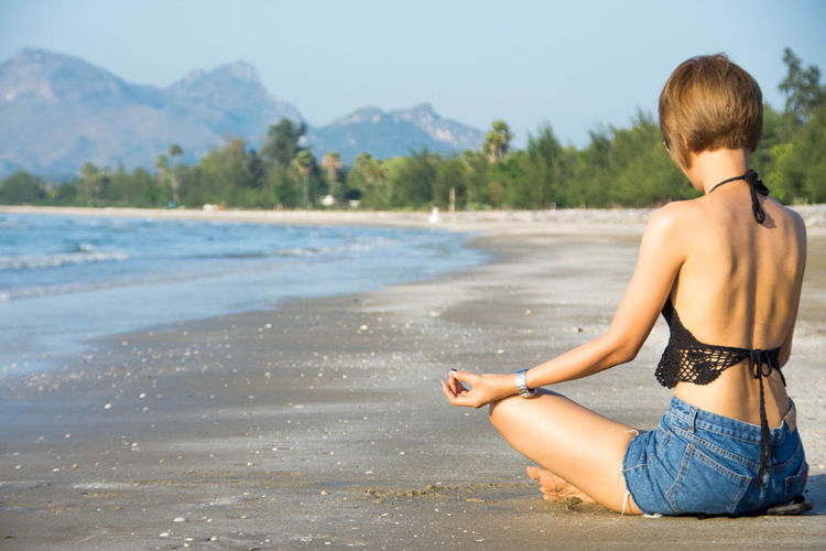Young woman sitting on sea shore against sky