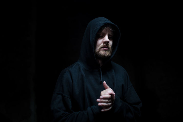 Man with hands clasped against black background