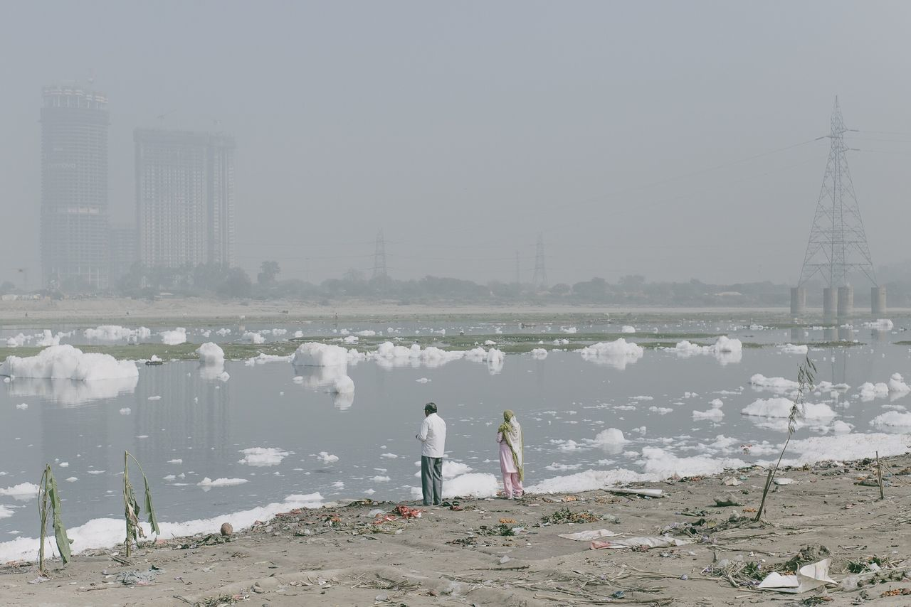 Rear View Of People Standing On Shore Against Sky