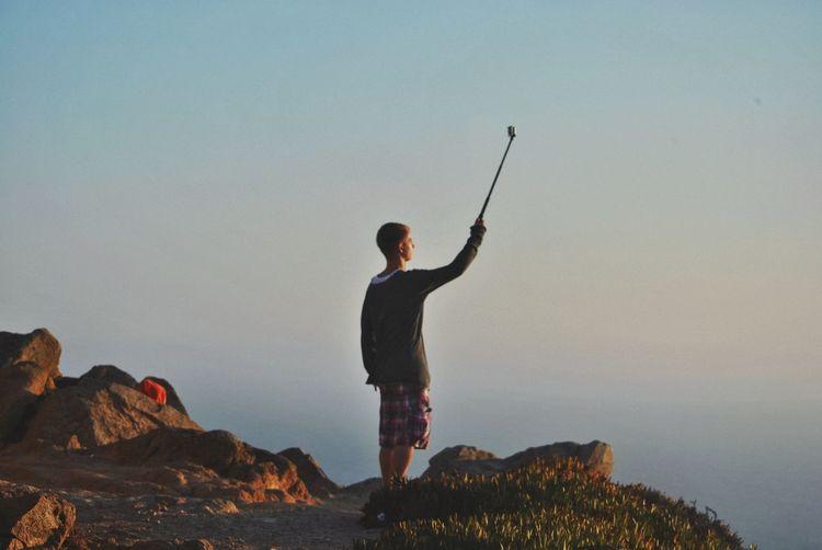 Full length of man taking selfie while standing on mountain against sky