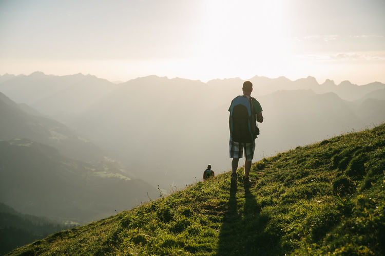 Mountain Rear View Real People Beauty In Nature Scenics - Nature Full Length Tranquility Nature Mountain Range Leisure Activity One Person Tranquil Scene Lifestyles Plant Sky Non-urban Scene Green Color Men Sunlight Hiking Outdoors Sun Lens Flare Looking At View Sunset