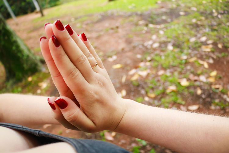 Midsection of woman doing yoga with hands clasped on field