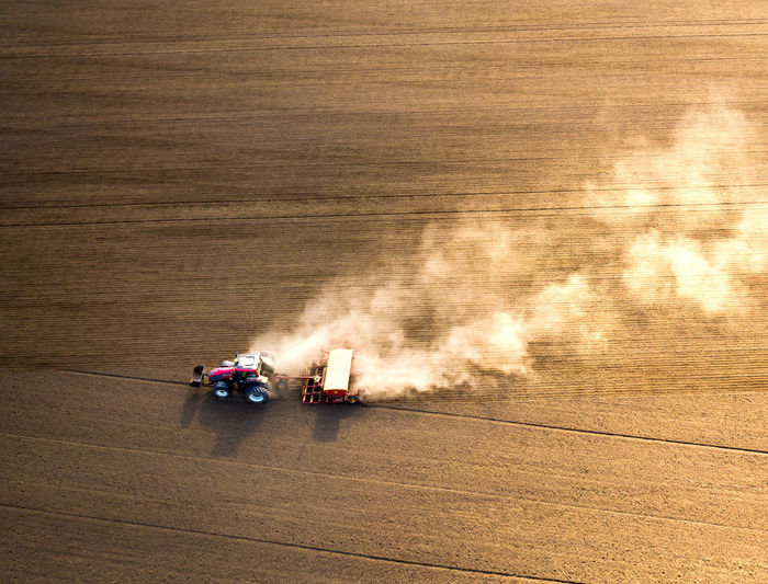 Tractor Working in the Fields Water Combine Harvester Sunset Aerial View Tractor Agricultural Machinery Farm Barley Crop  Wheat Plough Harvesting Cereal Plant Off-road Vehicle Agricultural Field Cultivated Land Bale  Agricultural Equipment Farmland Plowed Field Vehicle Trailer