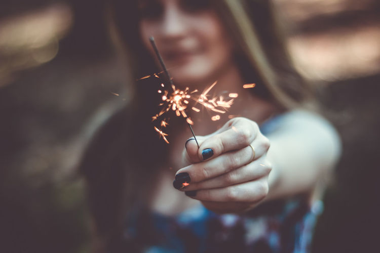 Close-up of woman holding sparkler