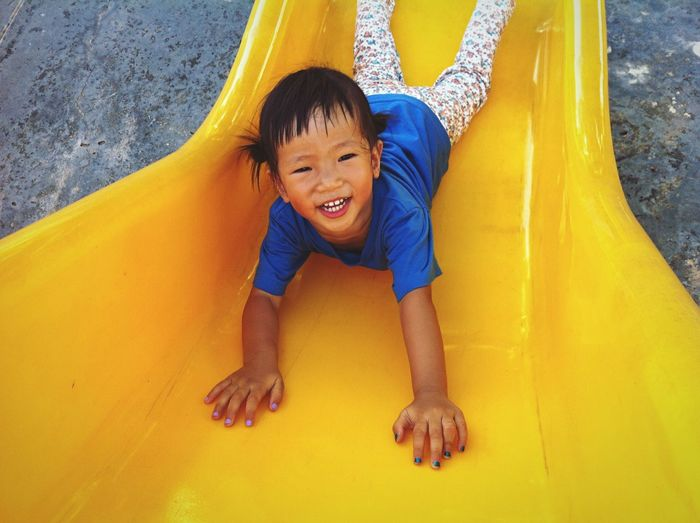 Portrait of happy girl playing on yellow slide in playground