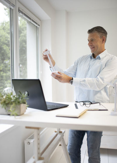 Man using phone while standing on table