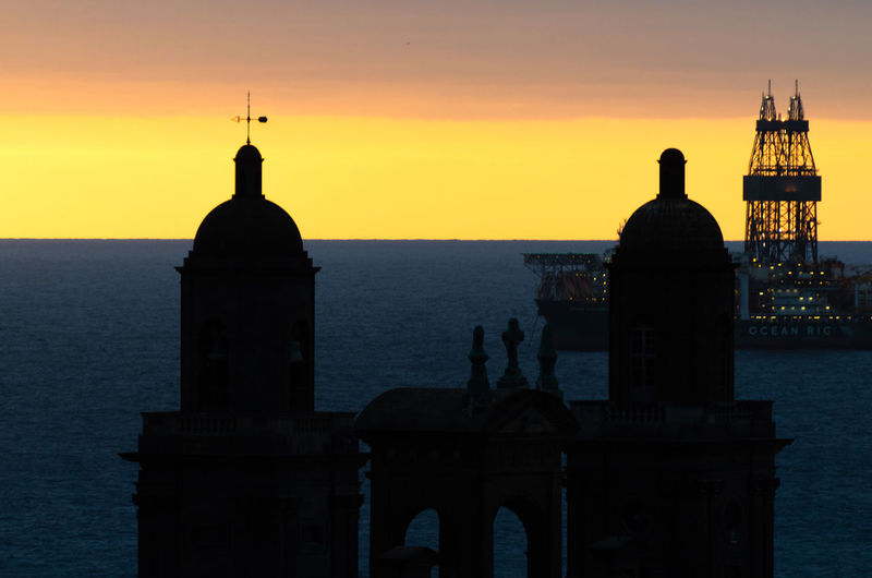 Silhouette of building by sea against sky during sunset